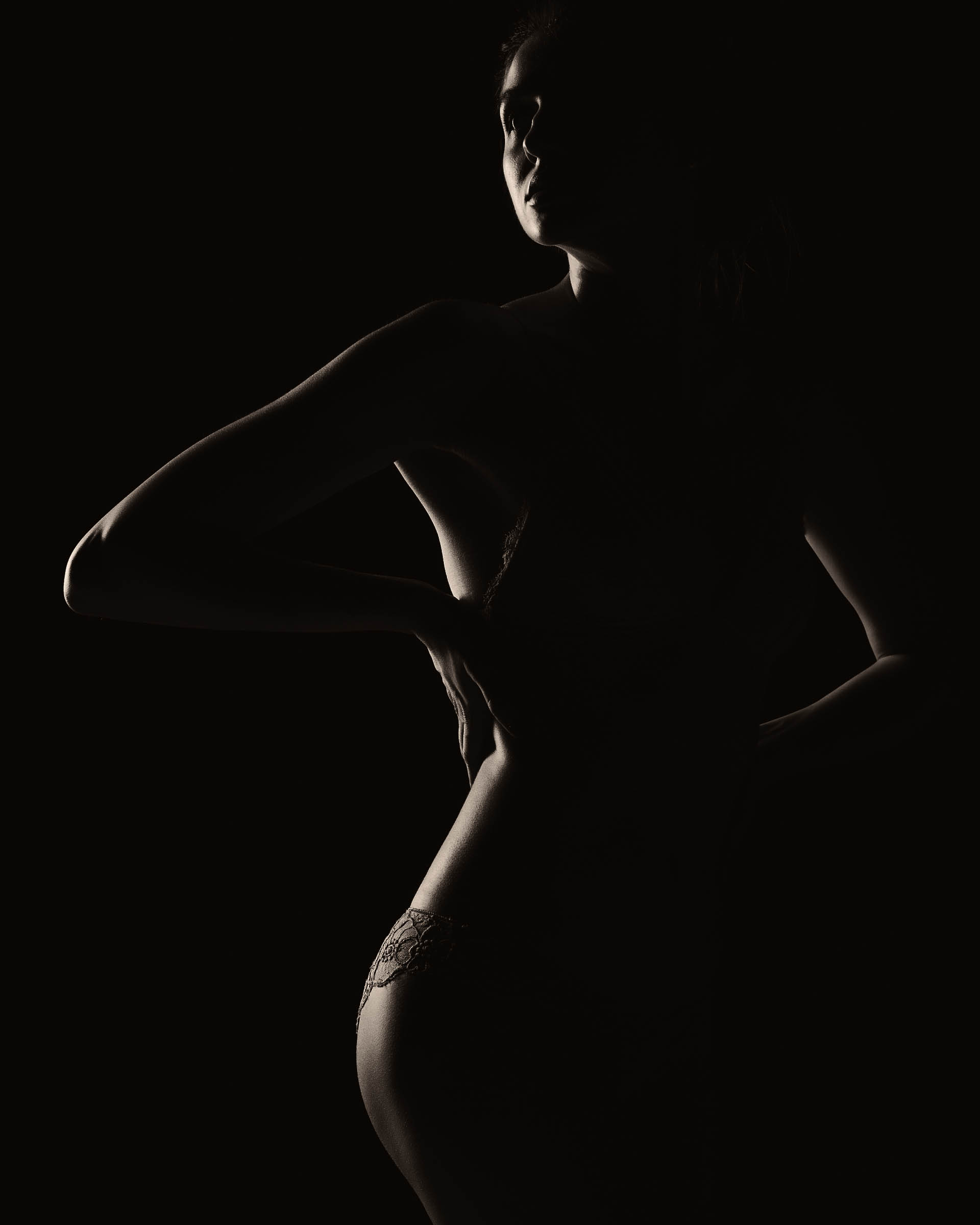 Black and white silhouette of young, sporty and sexy woman in lingerie on black studio background